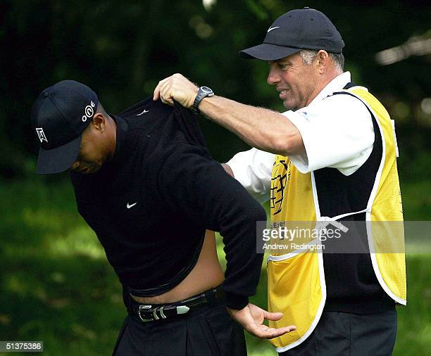 Tiger Woods of the United States has some cream rubbed into his injured back by caddy Steve Williams on the fourth hole during the first round of the...