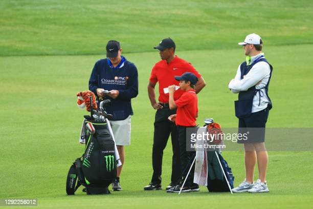 Tiger Woods of the United States, his son and playing partner Charlie Woods and their caddies Joe LaCava and his son Joe LaCava Jr. Look on from the...