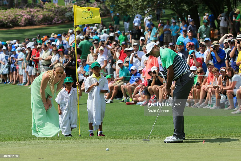 Tiger Woods of the United States hits a putt as his girlfriend Lindsey Vonn, son Charlie and daughter Sam look on during the Par 3 Contest prior to the start of the 2015 Masters Tournament at Augusta National Golf Club on April 8, 2015 in Augusta, Georgia.