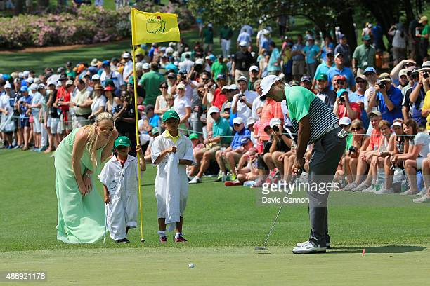 Tiger Woods of the United States hits a putt as his girlfriend Lindsey Vonn, son Charlie and daughter Sam look on during the Par 3 Contest prior to...