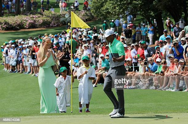 Tiger Woods of the United States hits a putt as his girlfriend Lindsey Vonn son Charlie and daughter Sam look on during the Par 3 Contest prior to...