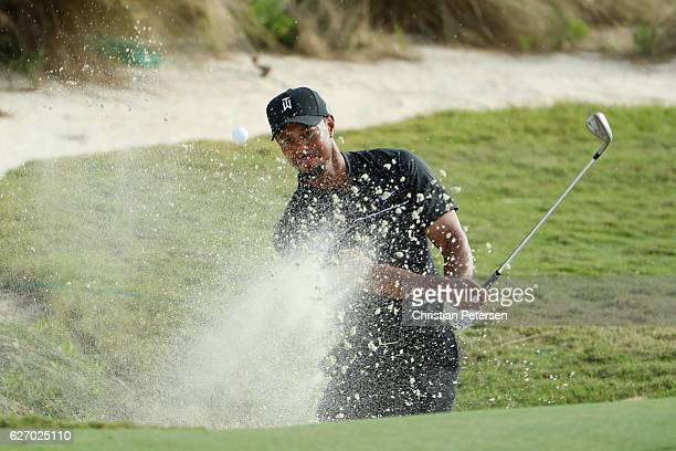 Tiger Woods of the United States hits a shot from a greenside bunker on the 14th hole during round one of the Hero World Challenge at Albany The...