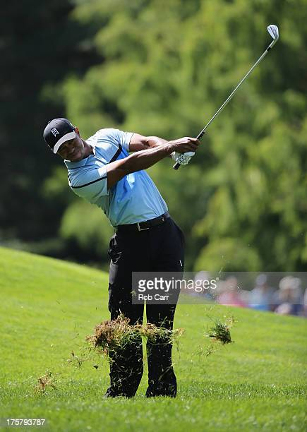 Tiger Woods of the United States hits a shot from the rough on the fourth hole during the first round of the 95th PGA Championship on August 8, 2013...