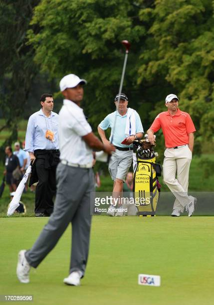 Tiger Woods of the United States hits a shot on the 14th teeas Sergio Garcia of Spain looks on during a practice round prior to the start of the...