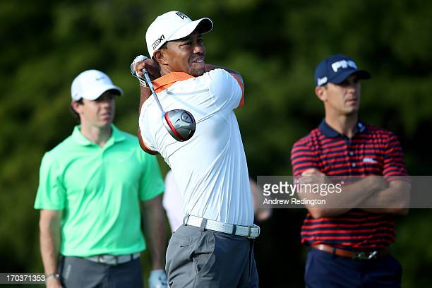 Tiger Woods of the United States hits a tee shot as Rory McIlroy of Northern Ireland and Billy Horschel of the United States look on during a...