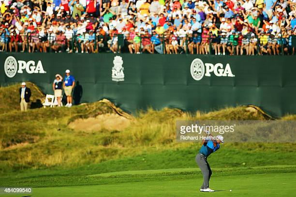 Tiger Woods of the United States hits his second shot on the 18th hole during the continuation of the weather-delayed second round of the 2015 PGA...