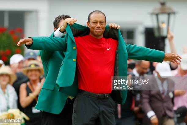 Tiger Woods of the United States is awarded the Green Jacket by Masters champion Patrick Reed during the Green Jacket Ceremony after winning the...