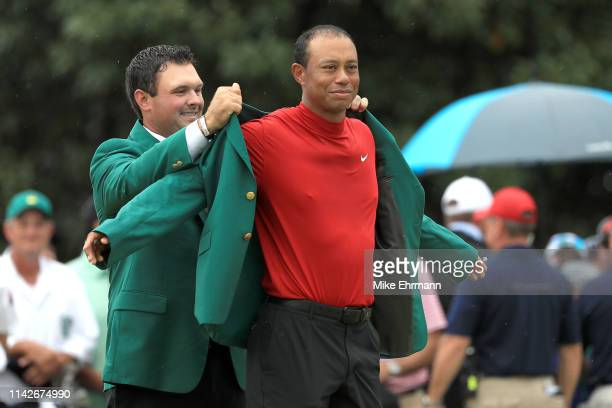 Tiger Woods of the United States is awarded the Green Jacket by Patrick Reed of the United States during the Green Jacket Ceremony after winning the...