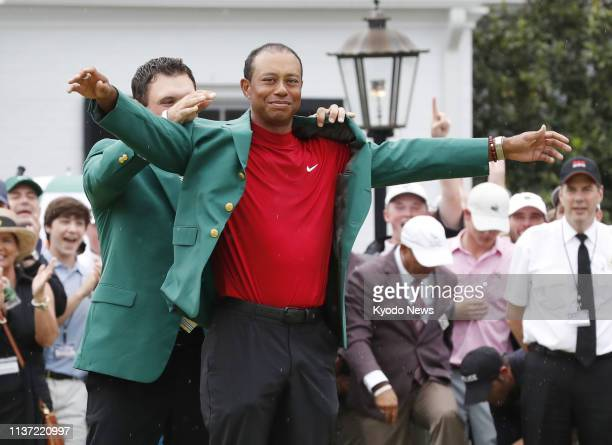 Tiger Woods of the United States is awarded the Green Jacket by the previous year's Masters champion Patrick Reed after winning the 2019 tournament...