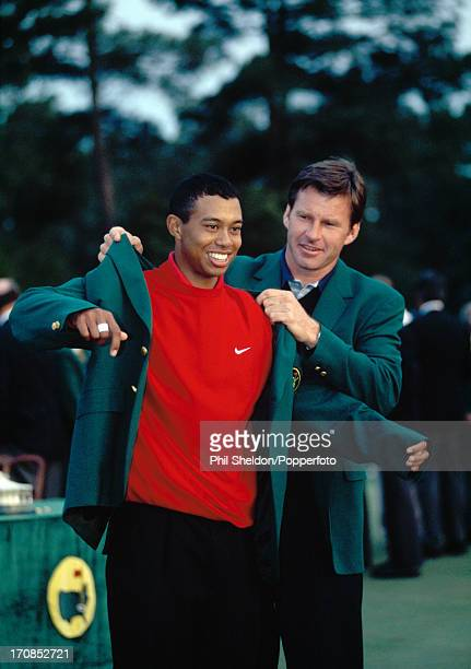 Tiger Woods of the United States is helped into the winner's Green Jacket by Nick Faldo after his victory in the US Masters Golf Tournament held at...