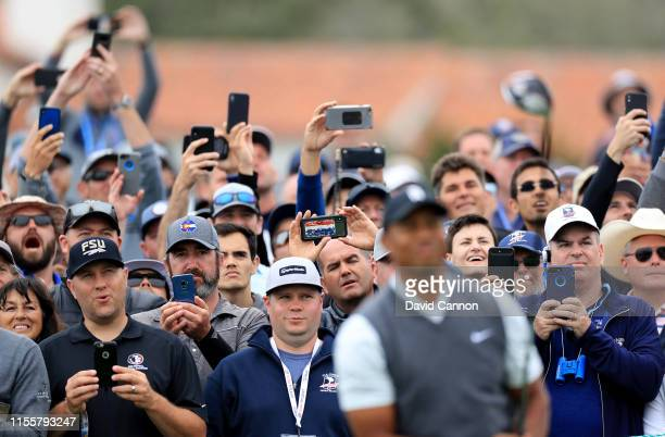 Tiger Woods of the United States is photographed by many fans using cell phones as he follows his tee shot on the par 4, 10th hole during the first...