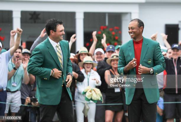 Tiger Woods of the United States is presented with his Green Jacket by 2018 Champion Patrick Reed during the Green Jacket presentation after his...
