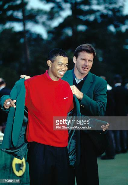 Tiger Woods of the United States is presented with the Green Jacket by Nick Faldo for his victory in the US Masters Golf Tournament held at the...