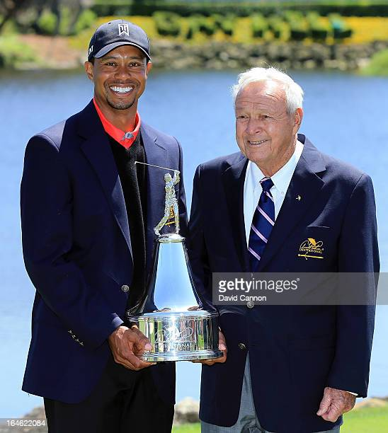 Tiger Woods of the United States is presented with the trophy by Arnold Palmer of the United States the win meant he regained the World's number one...