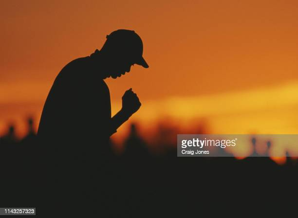 Tiger Woods of the United States is silhouetted against the setting sun as he makes a fist pump to celebrate a putt during the Phoenix Open golf...