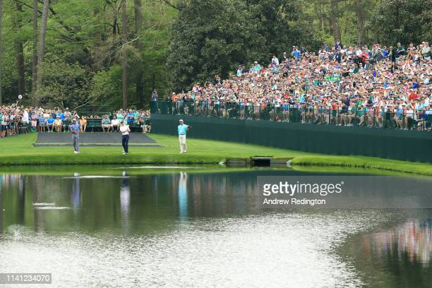 Tiger Woods of the United States Justin Thomas of the United States and Fred Couples of the United States skip balls across the water hazard on the...