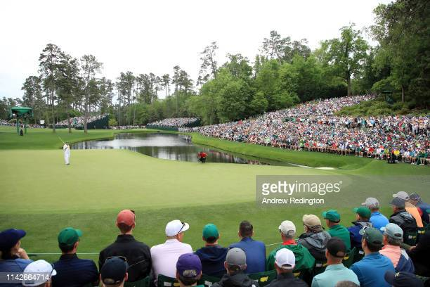 Tiger Woods of the United States lines up a putt for birdie on the 16th green as patrons look on during the final round of the Masters at Augusta...