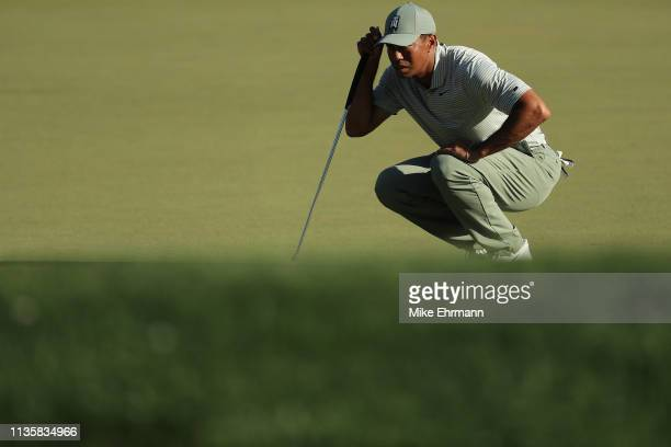 Tiger Woods of the United States lines up a putt on the 14th green during the first round of The PLAYERS Championship on The Stadium Course at TPC...