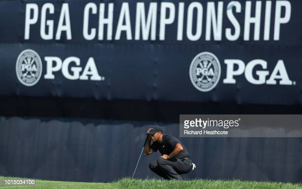 Tiger Woods of the United States lines up a putt on the 18th green during the continuation of the weather delayed second round of the 2018 PGA...