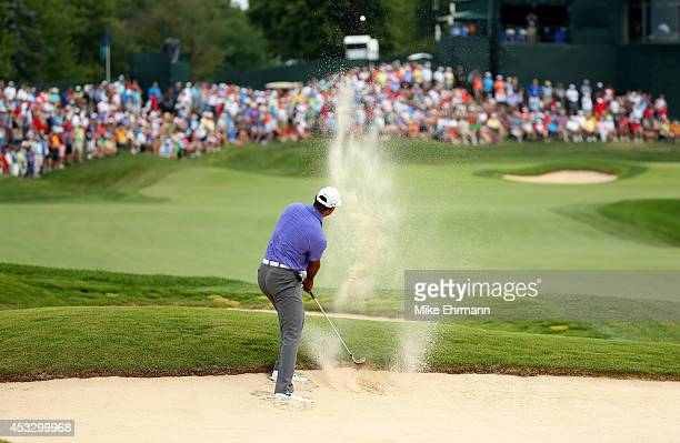 Tiger Woods of the United States plays a bunker shot on the 18th hole during the first round of the 96th PGA Championship at Valhalla Golf Club on...