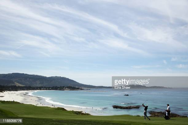 Tiger Woods of the United States plays a shot as caddie Joe LaCava looks on during a practice round prior to the 2019 US Open at Pebble Beach Golf...
