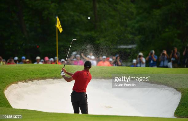 Tiger Woods of the United States plays a shot from a bunker on the 17th hole during the final round of the 2018 PGA Championship at Bellerive Country...