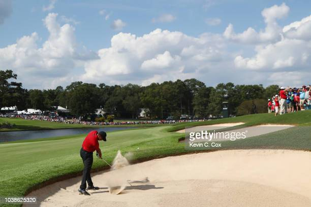 Tiger Woods of the United States plays a shot from a bunker on the eighth hole during the final round of the TOUR Championship at East Lake Golf Club...
