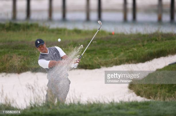 Tiger Woods of the United States plays a shot from a bunker on the 17th hole during the first round of the 2019 U.S. Open at Pebble Beach Golf Links...
