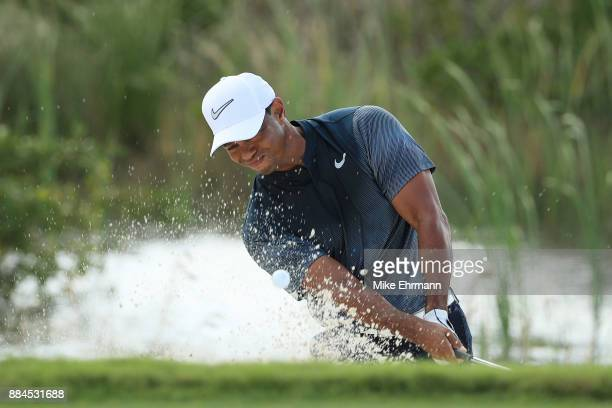 Tiger Woods of the United States plays a shot from a bunker on the fifth hole during the third round of the Hero World Challenge at Albany Bahamas on...