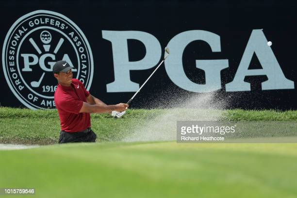 Tiger Woods of the United States plays a shot from a greenside bunker on the sixth hole during the final round of the 2018 PGA Championship at...