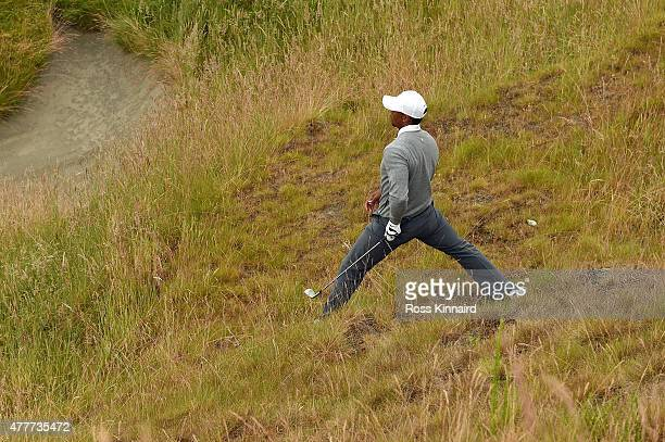 Tiger Woods of the United States plays a shot in the rough near the tenth green during the second round of the 115th US Open Championship at Chambers...