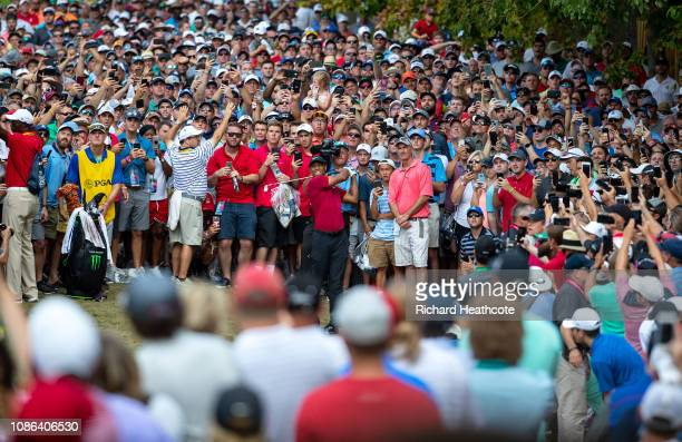 Tiger Woods of the United States plays a shot into the ninth green from the crowd during the final round of the 2018 PGA Championship at Bellerive...