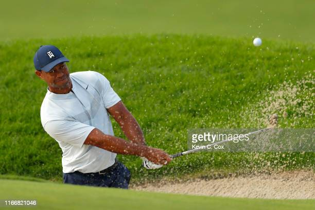Tiger Woods of the United States plays a shot out of a bunker on the 12th hole during the first round of The Northern Trust at Liberty National Golf...