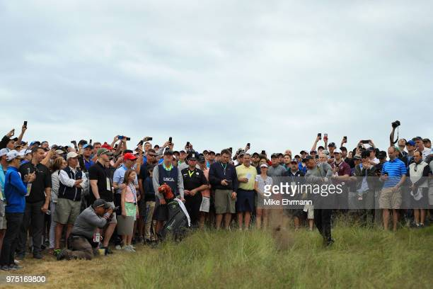 Tiger Woods of the United States plays a shot out of the fescue on the 12th hole as a gallery of fans look on during the second round of the 2018 US...