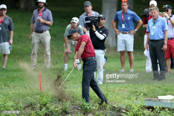 Tiger Woods of the United States plays his second shot on the 17th hole during the final round of the 100th PGA Championship at the Bellerive Country...