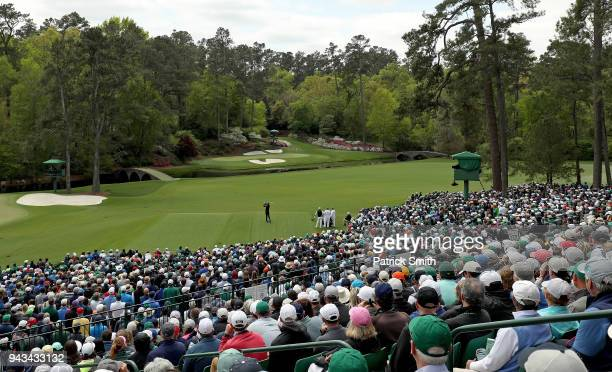 Tiger Woods of the United States plays his shot from the 12th tee as a gallery of patrons look on during the final round of the 2018 Masters...