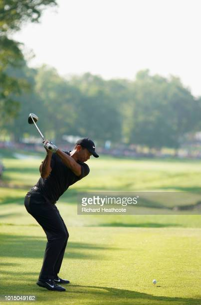 Tiger Woods of the United States plays his shot from the 17th tee during the continuation of the weather delayed second round of the 2018 PGA...