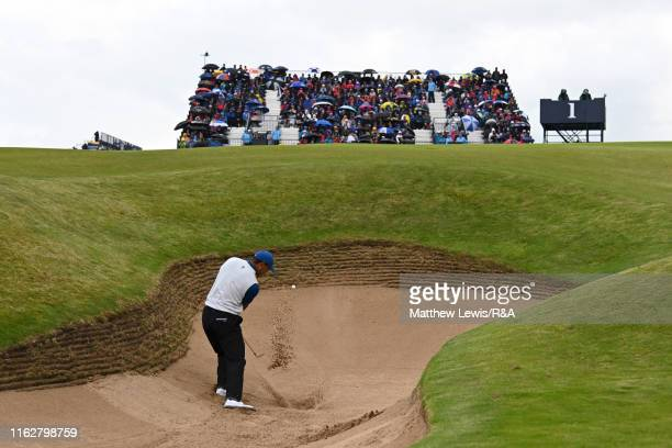 Tiger Woods of the United States plays his third shot on the first hole out of the bunker during the first round of the 148th Open Championship held...