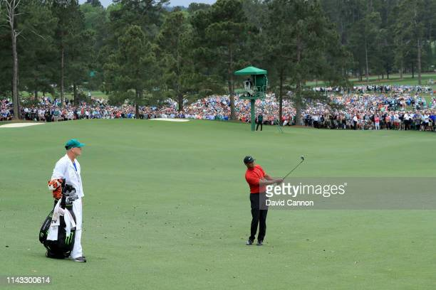Tiger Woods of the United States plays his third shot on the par 4, 18th hole as the huge crowds watch from down the fairway during the final round...