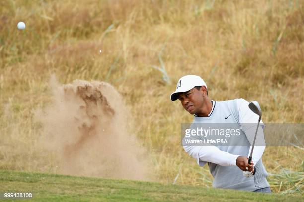 Tiger Woods of the United States plays out a bunker on the 1st hole while practicing during previews to the 147th Open Championship at Carnoustie...