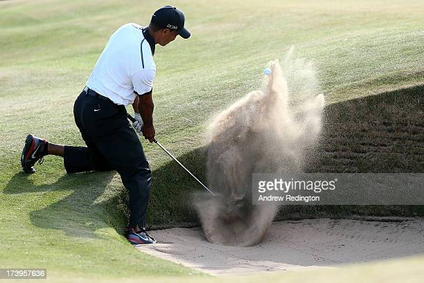 Tiger Woods of the United States plays out of a bunker on the 12th hole during the first round of the 142nd Open Championship at Muirfield on July 18...