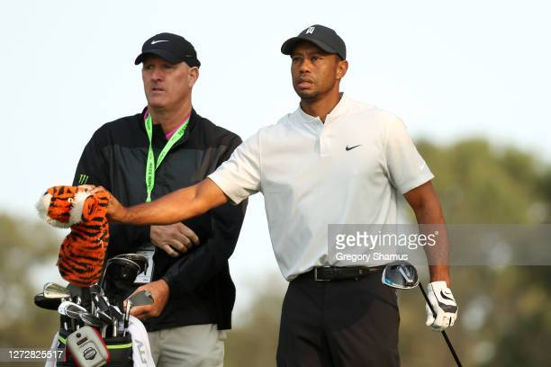 Tiger Woods of the United States pulls a club from his bag next to caddie Joe LaCava during a practice round prior to the 120th U.S. Open...