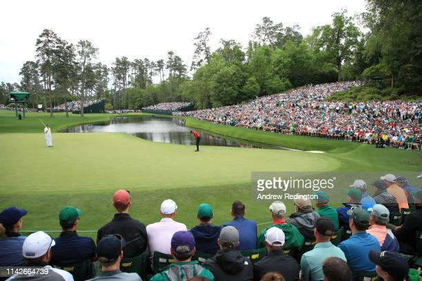 Tiger Woods of the United States putts for birdie on the 16th green as patrons look on during the final round of the Masters at Augusta National Golf...