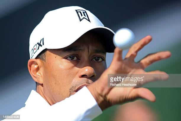 Tiger Woods of the United States reaches for a golf ball on the practice ground during the third practice round prior to the start of the 141st Open...