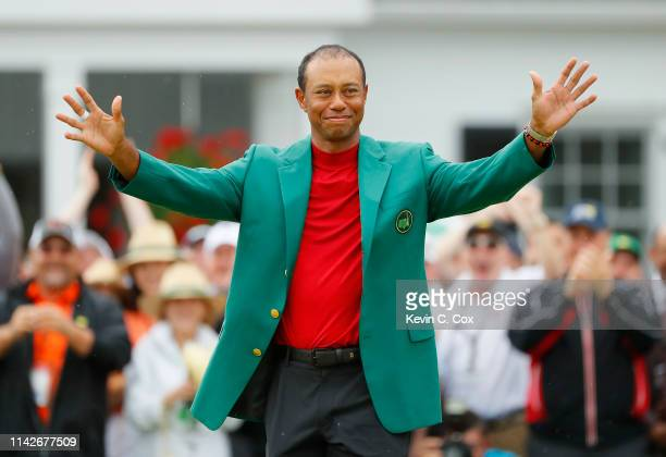 Tiger Woods of the United States reacts after being awarded the Green Jacket during the Green Jacket Ceremony after winning the Masters at Augusta...