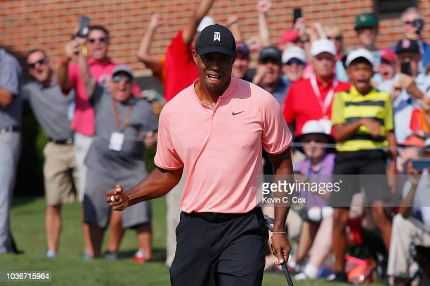Tiger Woods of the United States reacts after making a putt for eagle on the 18th green during the first round of the TOUR Championship at East Lake...