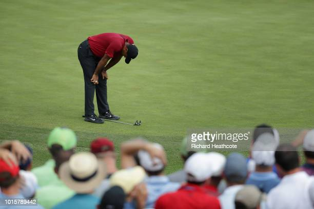 Tiger Woods of the United States reacts after missing a putt for birdie on the 11th green during the final round of the 2018 PGA Championship at...