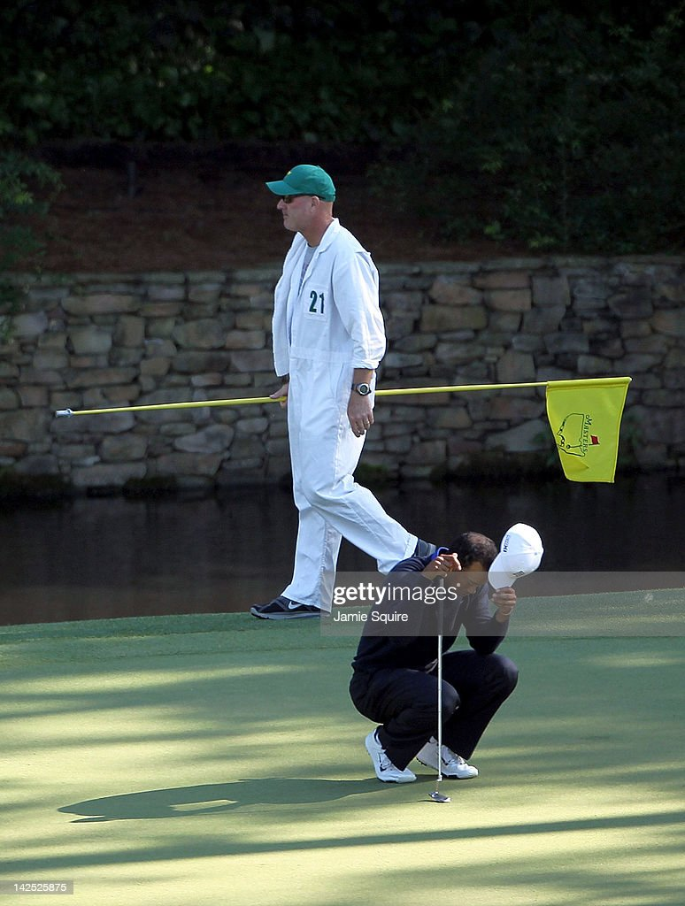 Tiger Woods of the United States reacts after missing a putt on the 11th hole as his caddie Joe LaCava looks on during the second round of the 2012 Masters Tournament at Augusta National Golf Club on April 6, 2012 in Augusta, Georgia.