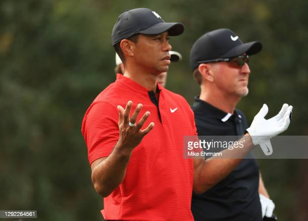 Tiger Woods of the United States reacts to Charlie Woods' tee shot as David Duval of the United States looks on during the final round of the PNC...
