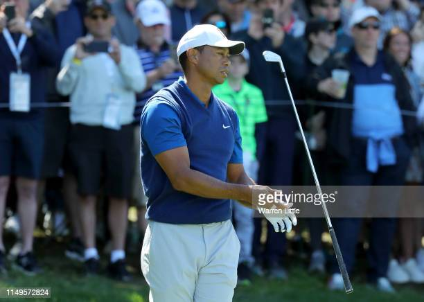 Tiger Woods of the United States reacts to his tee shot on the 17th hole during the first round of the 2019 PGA Championship at the Bethpage Black...